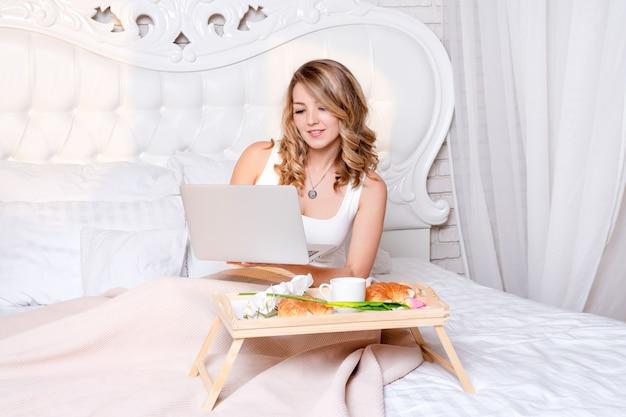Młoda ładna blond kobieta siedzi na łóżku z laptopa o śniadanie, freelancer lub blogger w domu. kobieta pracuje na komputerze z domu.