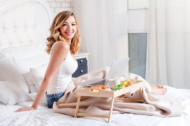 Młoda ładna blond kobieta siedzi na łóżku z laptopa o śniadanie, freelancer lub blogger w domu.