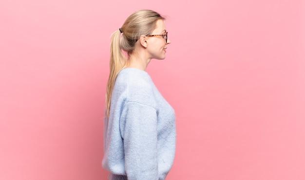 Młoda ładna blond kobieta w widoku profilu, chcąca skopiować przestrzeń do przodu, myśląc, wyobrażając sobie lub marząc na jawie