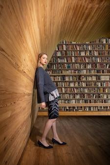 Młoda ładna blond studentka pozuje w nowoczesnym centrum zasobów edukacyjnych przed ogromnym regałem.