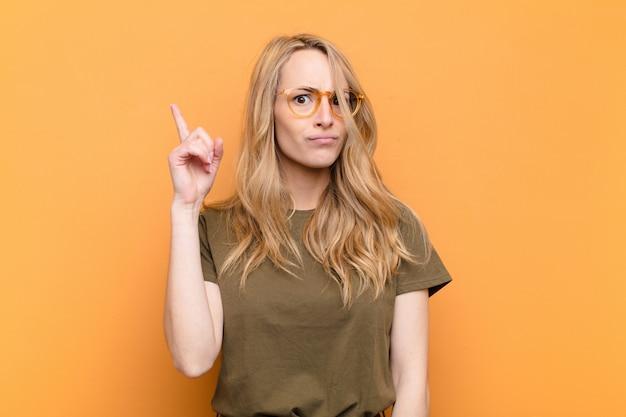 Młoda ładna blondynka czuje się jak geniusz, który dumnie trzyma palec w powietrzu po zrealizowaniu świetnego pomysłu, mówiąc: eureka o płaskiej ścianie