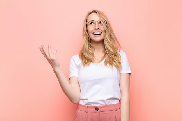 Młoda ładna blondynka czuje się szczęśliwa, zdziwiona i wesoła, uśmiechnięta z pozytywnym nastawieniem, realizująca rozwiązanie lub pomysł na płaskiej ścianie w kolorze