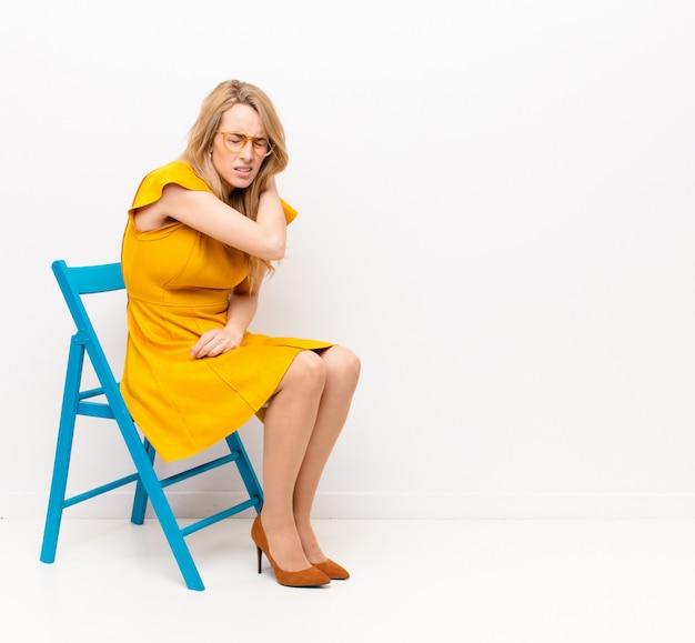 Młoda ładna blondynka czuje się zmęczona, zestresowana, niespokojna, sfrustrowana i przygnębiona, cierpi z powodu bólu pleców lub szyi na ścianę o płaskim kolorze