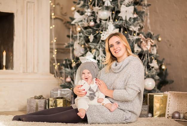 Młoda ładna blondynka matka pozuje z jej małym chłopcem na tle bożego narodzenia