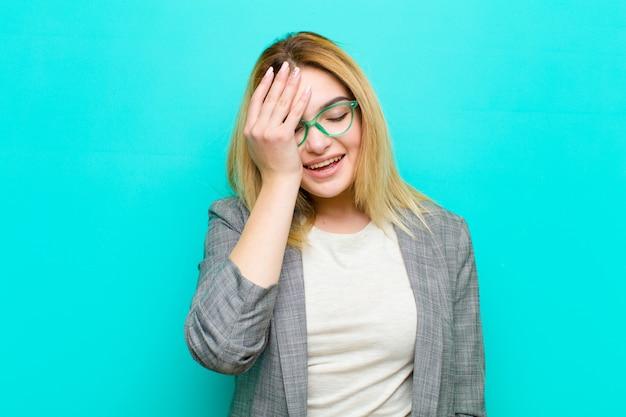 """Młoda ładna blondynka śmiejąca się i uderzająca w czoło, jak mówiąc: """"och!""""! zapomniałem lub to był głupi błąd w stosunku do płaskiej ściany"""