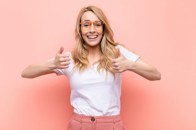 Młoda ładna blondynka uśmiechnięta szeroko, szczęśliwa, pozytywnie nastawiona, pewna siebie i odnosząca sukcesy, z oboma kciukami skierowanymi w górę na płaskiej, kolorowej ścianie