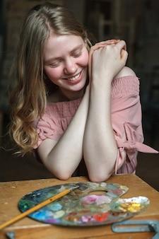 Młoda ładna blondynka w różowej sukience z falowanymi włosami trzyma ręce razem i śmieje się z przedniej palety w pracowni artystycznej