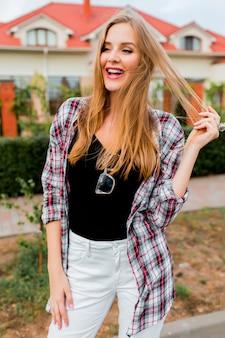 Młoda ładna blondynka wesoła dziewczyna z zaskoczoną twarzą szuka, pozuje na wsi w ciepły słoneczny wiosenny dzień. zabawna emocjonalna twarz.