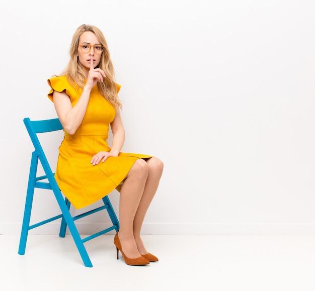 Młoda ładna blondynka wygląda poważnie i krzyżuje palcem na ustach, domagając się ciszy lub spokoju, zachowując tajemnicę nad kolorową ścianą
