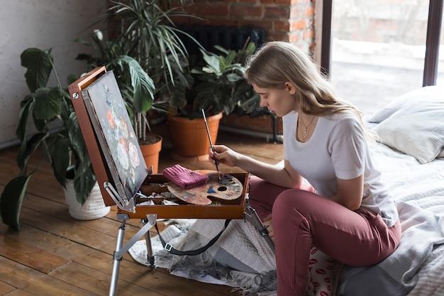 Młoda ładna blondynki dziewczyna siedzi blisko sztalugowego rysunku obrazka w studiu z muśnięciem i paletą