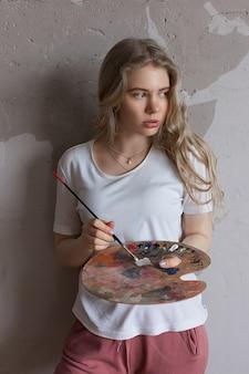 Młoda ładna blondynki dziewczyna z muśnięciem miesza kolory na palecie