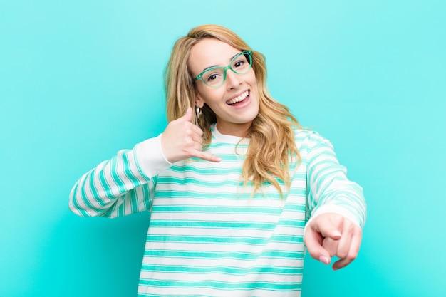 Młoda ładna blondynki kobieta ono uśmiecha się radośnie i wskazuje kamera podczas gdy dzwoniący ty później gestykulujesz, opowiada na telefonie przeciw płaskiej kolor ścianie