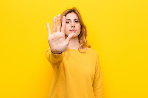 Młoda ładna blondynki kobieta patrzeje poważnego, srogiego, niezadowolonego i gniewnego seansu otwartej dłoni robi przerwie, gestykuluje przeciw kolor żółty ścianie