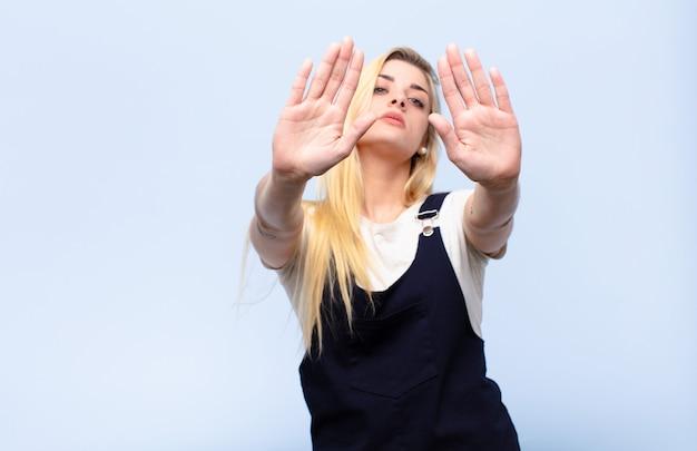 Młoda ładna blondynki kobieta patrzeje poważnego zabraniającego wejście z oba otwartymi palmami przeciw płaskiej ścianie