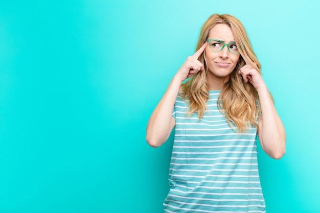 Młoda ładna blondynki kobieta patrzeje skoncentrowaną i intensywnie zastanawia się nad pomysłem, wyobrażając sobie rozwiązanie problemu lub problemu z kolorową ścianą