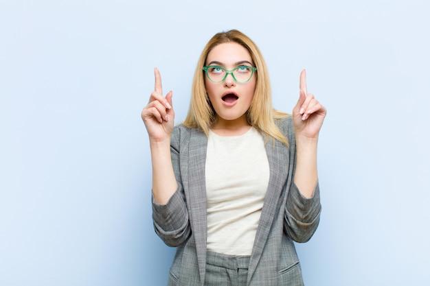 Młoda ładna blondynki kobieta patrzeje zszokowana, zdziwiona i otwarta, z ustami skierowana w górę obiema rękami do płaskiej ściany copyspace