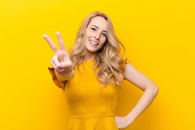 Młoda ładna blondynki kobieta uśmiechnięta i patrzeje szczęśliwa, beztroska i pozytywna, gestykulujący zwycięstwo lub pokój z jedną ręką przeciw kolor ścianie