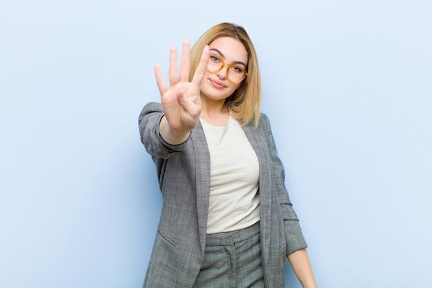 Młoda ładna blondynki kobieta uśmiechnięta i patrzeje życzliwa, pokazuje liczbę cztery lub czwarty z ręką naprzód, odliczający w dół przeciw płaskiej ścianie