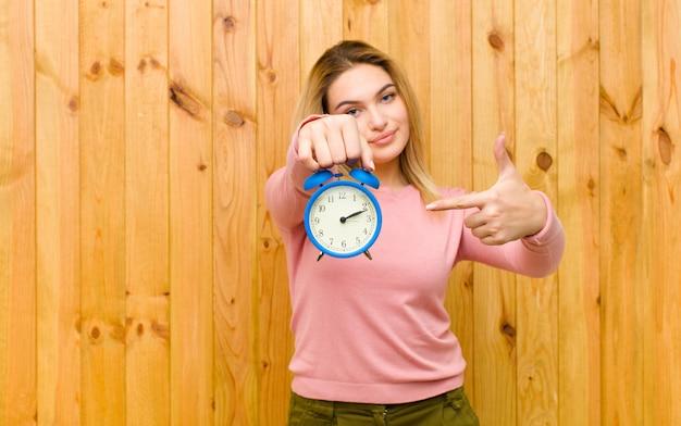 Młoda ładna blondynki kobieta z budzikiem na drewno ścianie