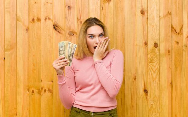 Młoda ładna blondynki kobieta z dolarowymi banknotami na drewno ścianie