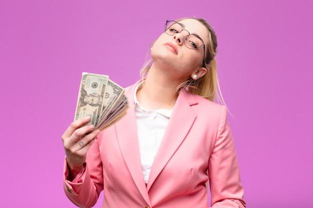 Młoda ładna blondynki kobieta z dolarowymi banknotami