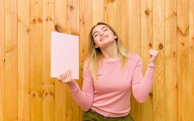 Młoda ładna blondynki kobieta z książkami przeciw drewno ścianie