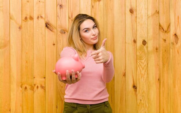 Młoda ładna blondynki kobieta z prosiątko bankiem na drewno ścianie