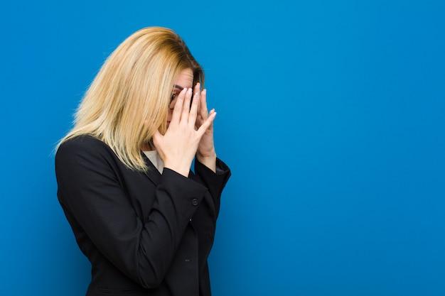 Młoda ładna blondynki kobieta zakrywająca usta rękami z zszokowanym, zdziwionym wyrazem, trzymająca w tajemnicy lub mówiąca ups przeciwko mieszkanie