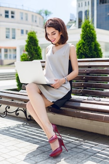 Młoda ładna brunetka bizneswoman siedzi na ławce w mieście. nosi szaro-czarną sukienkę i winne szpilki. ona pisze na laptopie.