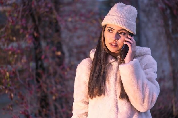 Młoda ładna brunetka rasy kaukaskiej w mieście dzwoni przez telefon, ubrana w różowy wełniany sweter i kapelusz. moda uliczna