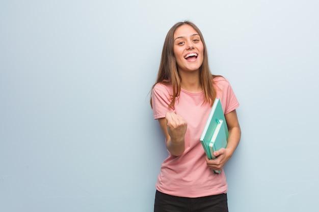 Młoda ładna caucasian kobieta zaskakująca i zszokowana. ona trzyma książki.