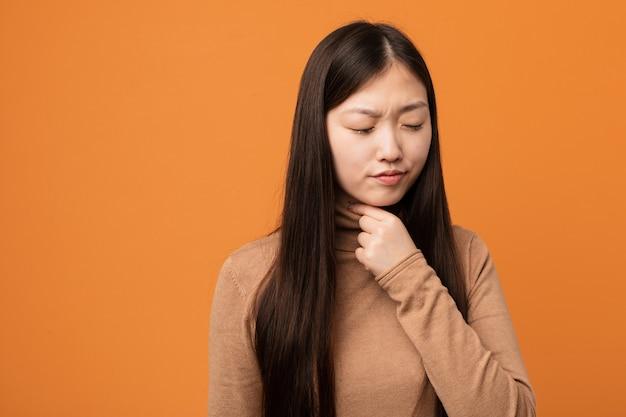 Młoda ładna chinka cierpi na ból gardła z powodu wirusa lub infekcji.