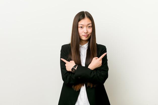 Młoda ładna chinka wskazuje bokiem i próbuje wybrać jedną z dwóch opcji.