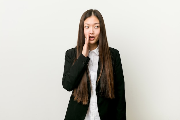 Młoda ładna chińska biznesowa kobieta mówi tajną gorącą hamującą wiadomość i patrzeje na boku