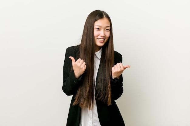 Młoda ładna chińska biznesowa kobieta podnosi oba aprobaty, uśmiechnięty i ufny.