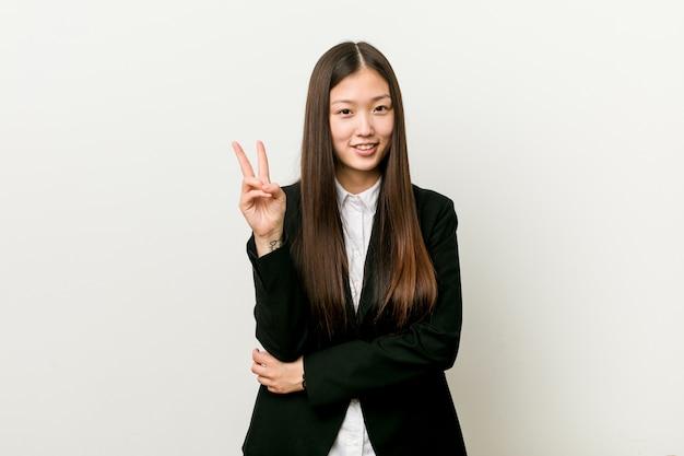 Młoda ładna chińska biznesowa kobieta pokazuje numer dwa z palcami.