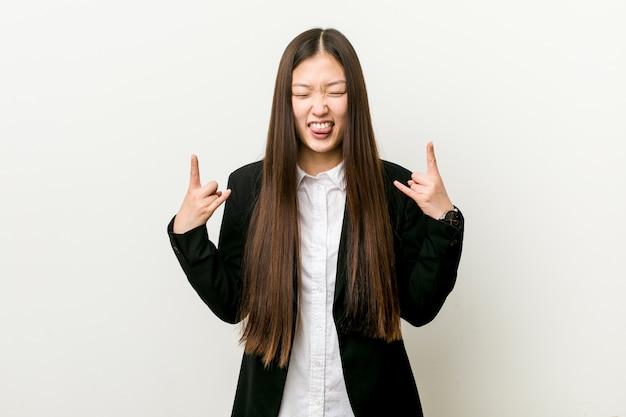 Młoda ładna chińska biznesowa kobieta pokazuje rockowego gest z palcami