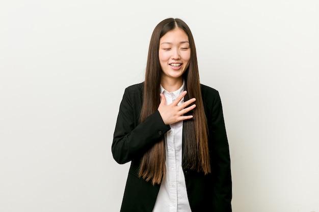 Młoda ładna chińska biznesowa kobieta śmieje się głośno, trzymając rękę na piersi.