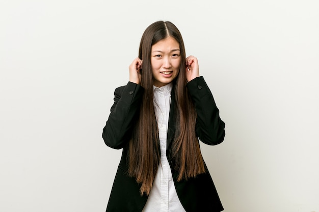 Młoda ładna chińska biznesowa kobieta zakrywa ucho z rękami.
