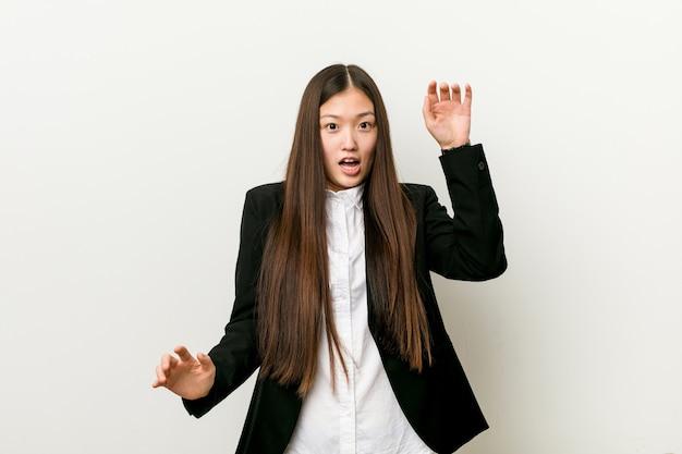 Młoda ładna chińska kobieta jest w szoku z powodu zbliżającego się niebezpieczeństwa