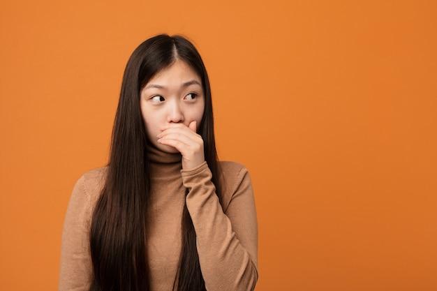 Młoda ładna chińska kobieta rozważny patrzeć odbitkowy astronautyczny nakrywkowy usta z ręką.
