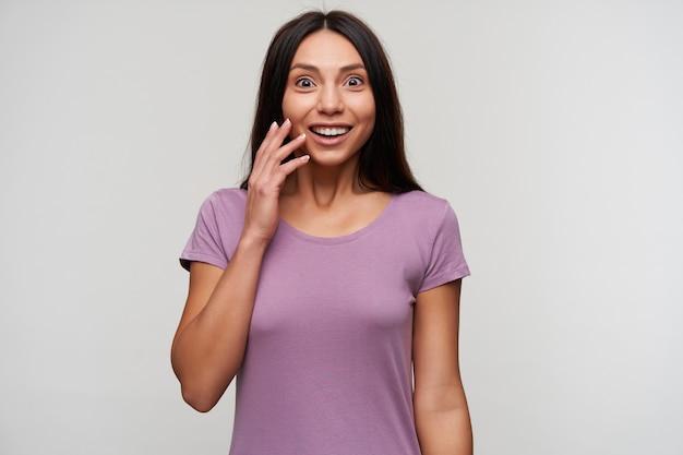 Młoda, ładna ciemnowłosa kobieta z otwartymi oczami z swobodnym makijażem podnosząca rękę do twarzy, patrząc zaskoczony, ubrana w fioletową koszulkę podczas pozowania