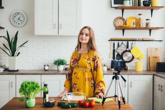 Młoda ładna ciężarna blogerka kręci filmem z przepisu na sałatkę aparatem w smartfonie