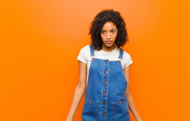 Młoda ładna czarna kobieta czuje się smutna, zdenerwowana lub zła i patrzy w bok z negatywnym nastawieniem, marszcząc brwi w sporze o pomarańczową ścianę