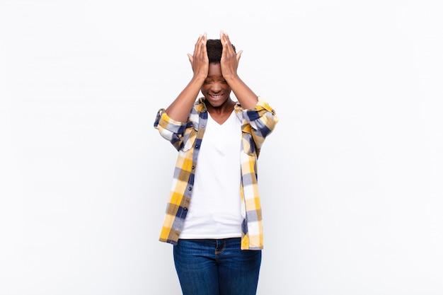 Młoda ładna czarna kobieta czuje się zestresowana i niespokojna, przygnębiona i sfrustrowana bólem głowy, podnosząc obie ręce do głowy