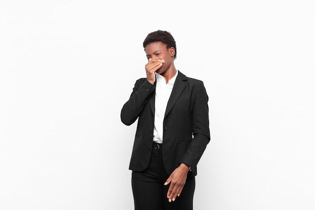Młoda, ładna, czarna kobieta czuje się zniesmaczona, trzymając nos, aby nie poczuć nieprzyjemnego i nieprzyjemnego smrodu na białej ścianie