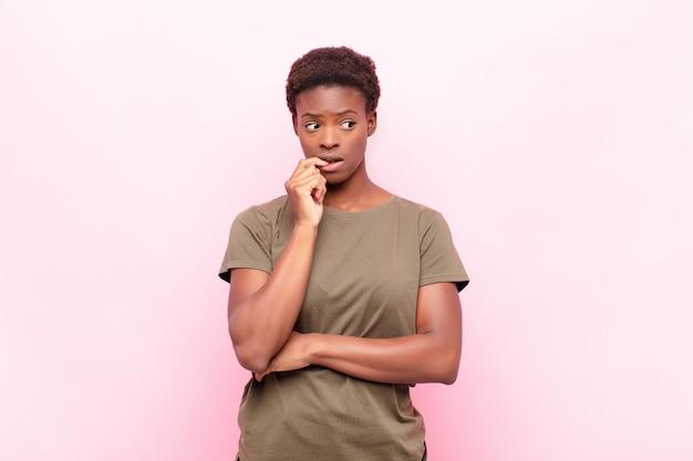 Młoda, ładna, czarna kobieta o zdziwionym, nerwowym, zmartwionym lub przestraszonym spojrzeniu, patrząc w bok w stronę miejsca na różową ścianę