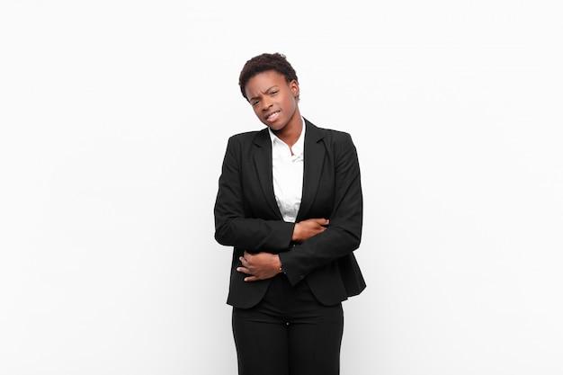 Młoda ładna czarna kobieta odczuwa niepokój, chory, chory i nieszczęśliwy, cierpi na bolesny ból brzucha lub grypę na białej ścianie