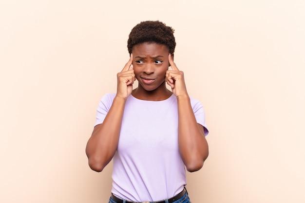 Młoda, ładna, czarna kobieta patrzy skoncentrowana i zastanawia się nad pomysłem, wyobrażając sobie rozwiązanie problemu lub problemu