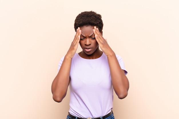 Młoda, ładna, czarna kobieta patrzy zestresowana i sfrustrowana, pracująca pod presją bólu głowy i niepokojona problemami
